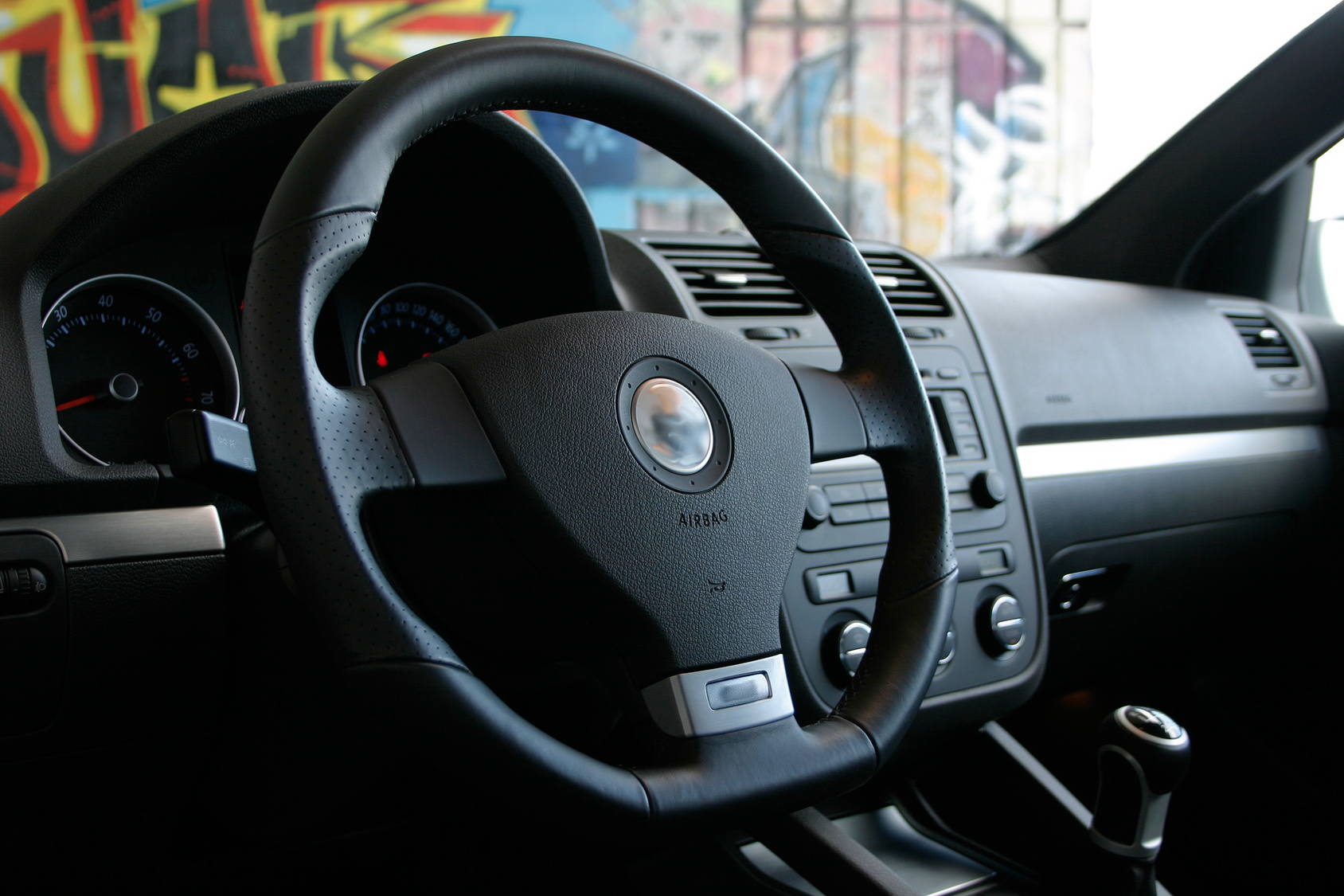 The interior steering wheel of a Volkswagen vehicle. Colorful walls in the background.