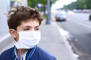 Boy wears medical mask outside